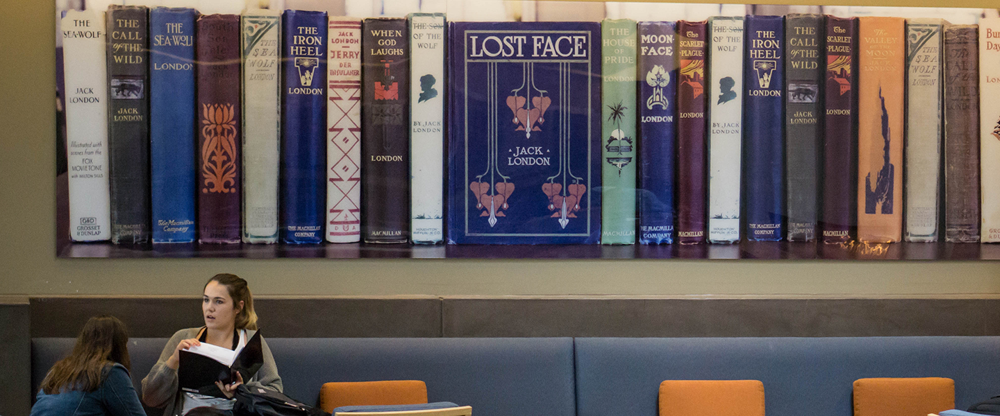 two students talk below a large wall art of spines of Jack London books